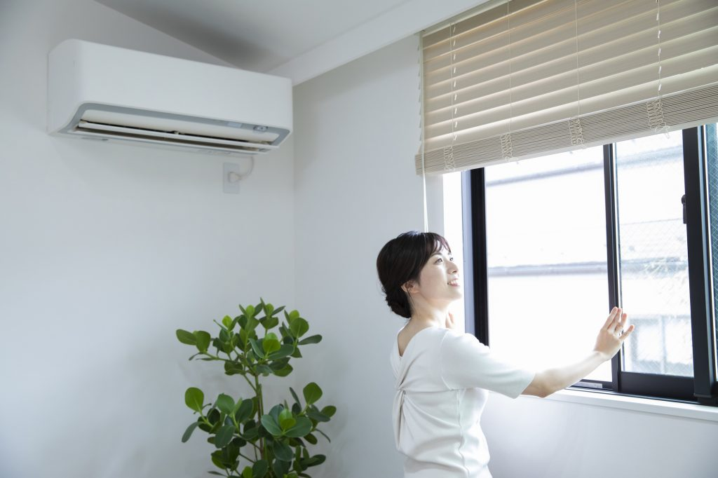窓換気をする女性とエアコン